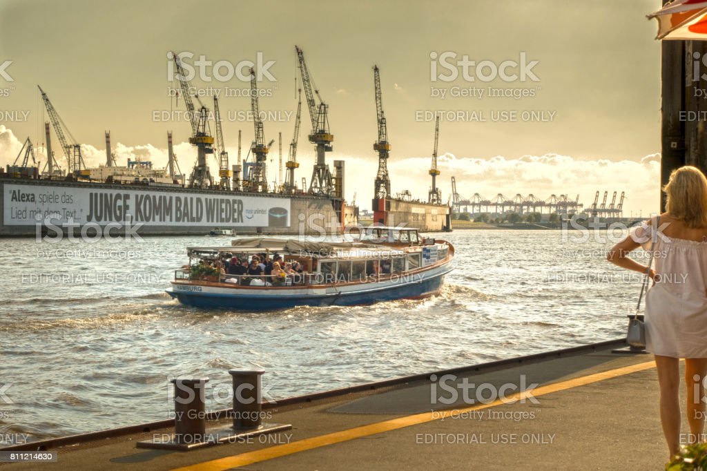 Old harbor ferry boat goes through the port of Hamburg with many...
