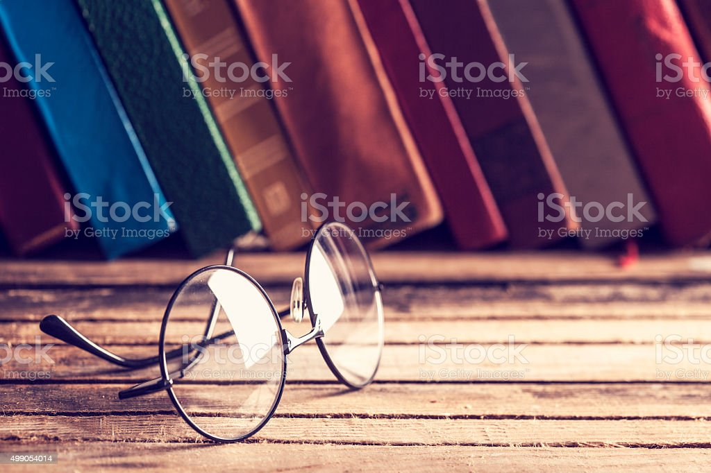 Old hardback books and eyeglasses stock photo