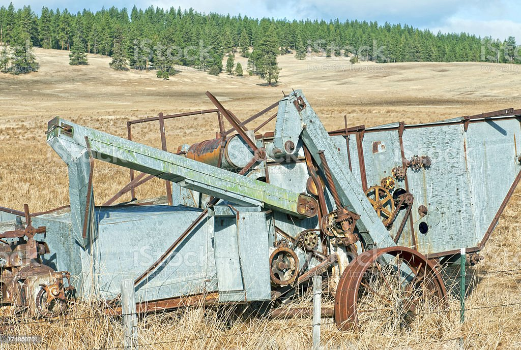 Old harvester near fence on high plateau in Oregon royalty-free stock photo