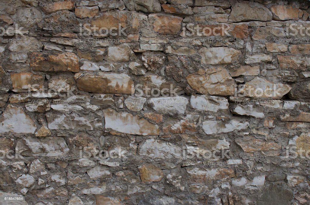 Old heaped stone wall full frame texture background stock photo