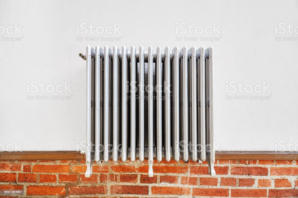 Old heating radiator on a wall stock photo