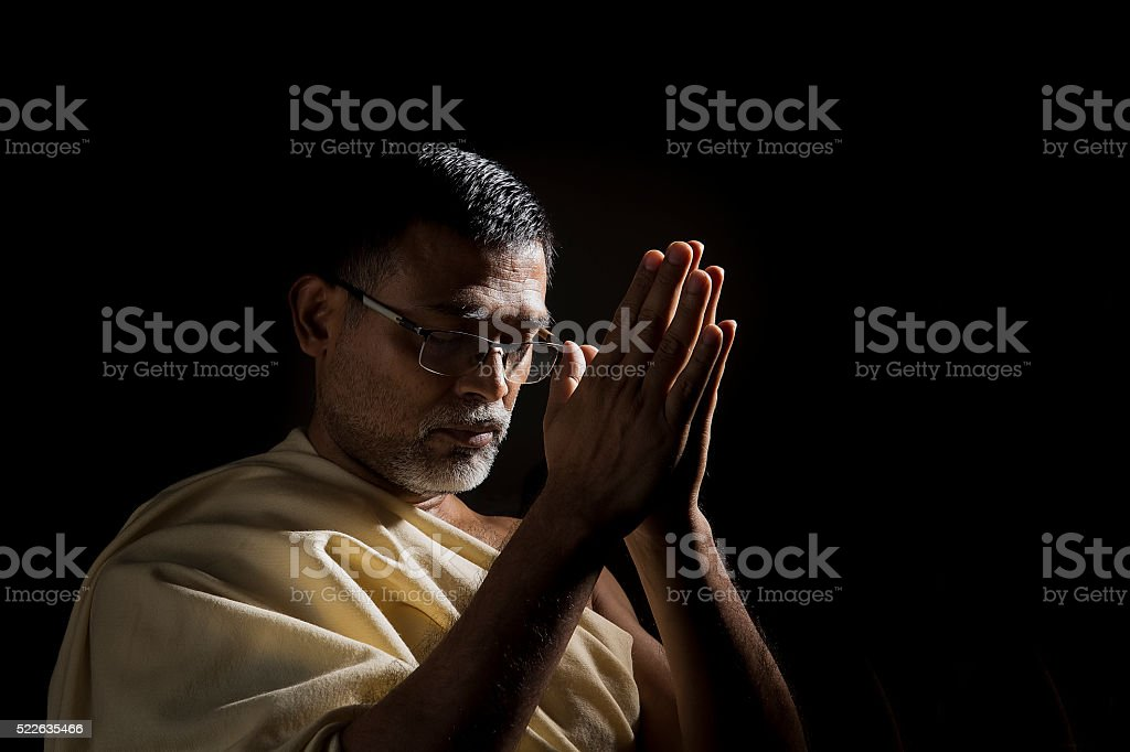 Old Hindu man praying with folded hands stock photo