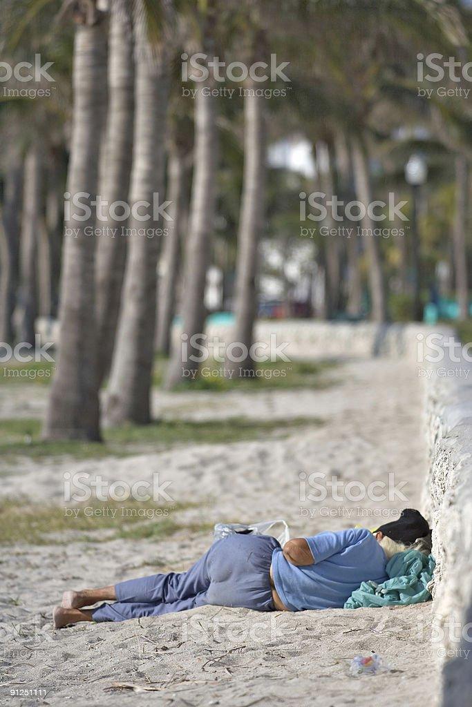 Old homeless woman sleeping on Miami Beach near Ocean Drive stock photo