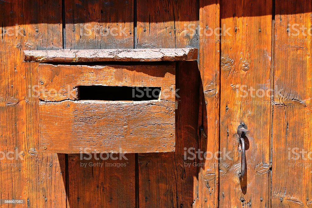 Old homemade wood stained mailbox on weathered door under sunlight stock photo