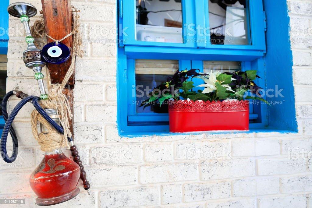 Old hookah hanging-blue window-red plantpot on white wall. Kas-Lycia-Turkey. 1452 stock photo