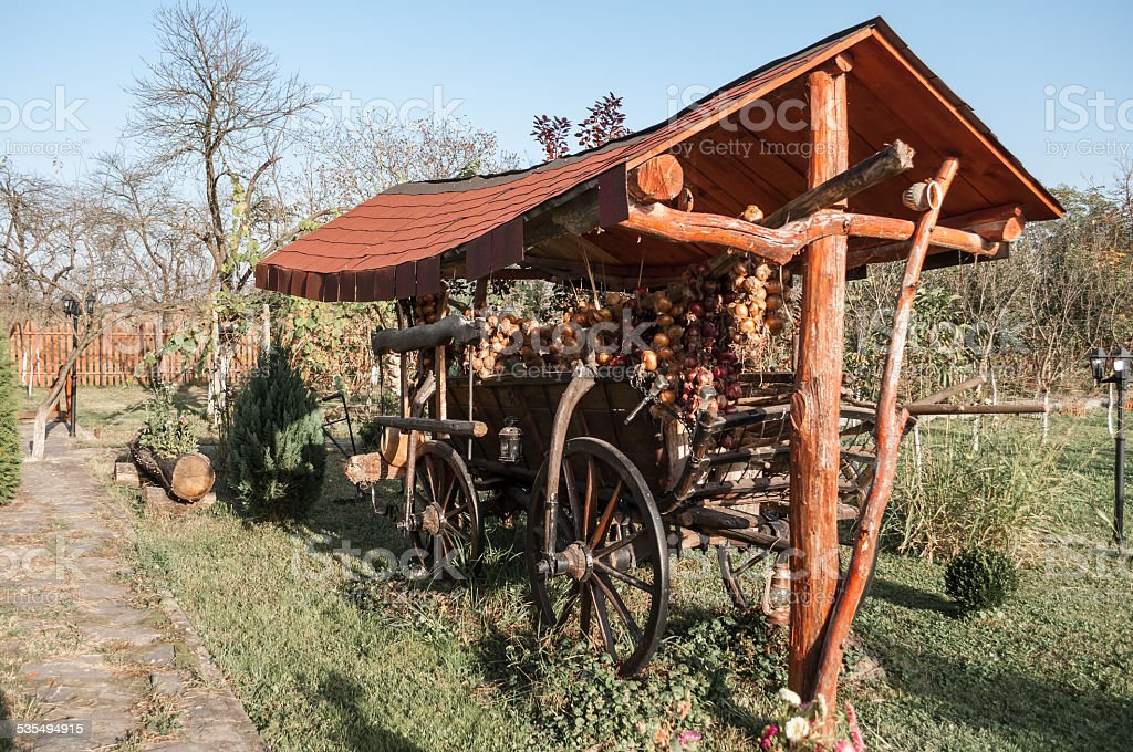 old horse cart decorated with onion ropes in a garden royalty-free stock photo