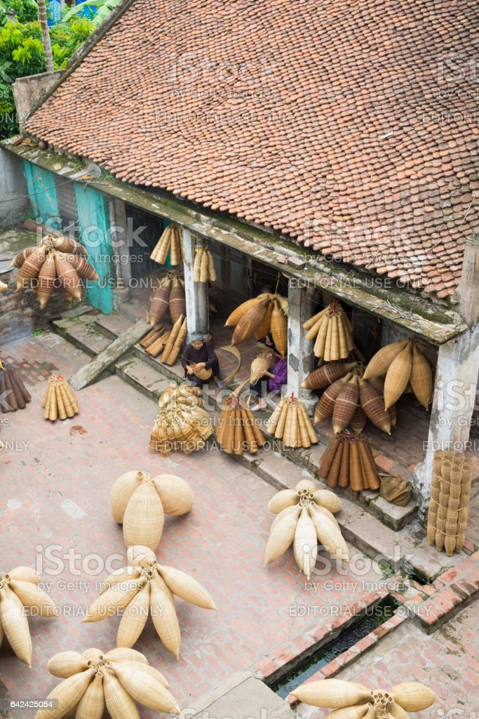 Hung Yen, Vietnam - July 26, 2015: Old house in country with old women weaves bamboo fish trap at Vietnamese traditional crafts village Thu Sy, Hung Yen province stock photo