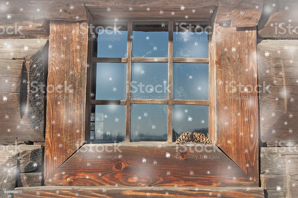 old house window in snow. snowflakes falling. wood background, planks. stock photo
