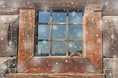 old house window in snow. snowflakes falling. wood background, planks.