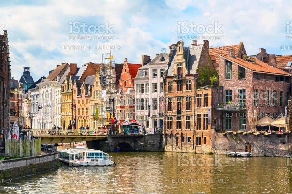 Old houses along canal and boat in Ghent, Belgium stock photo