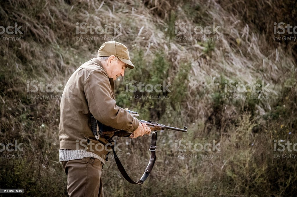 Old hunter reloads his rifle stock photo