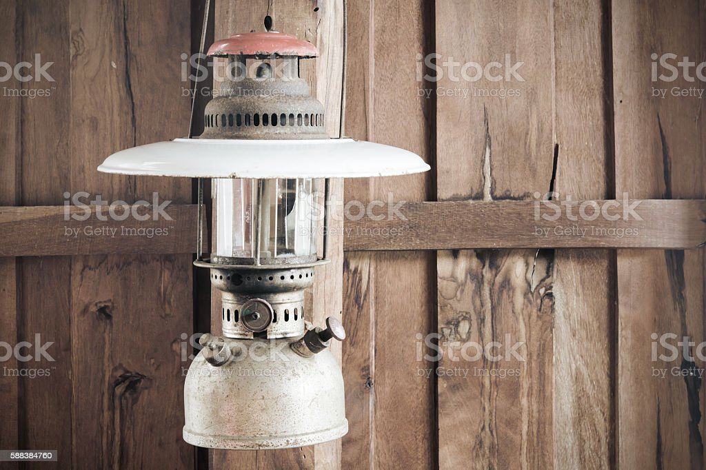 old hurricane lamp hanging on wooden stock photo