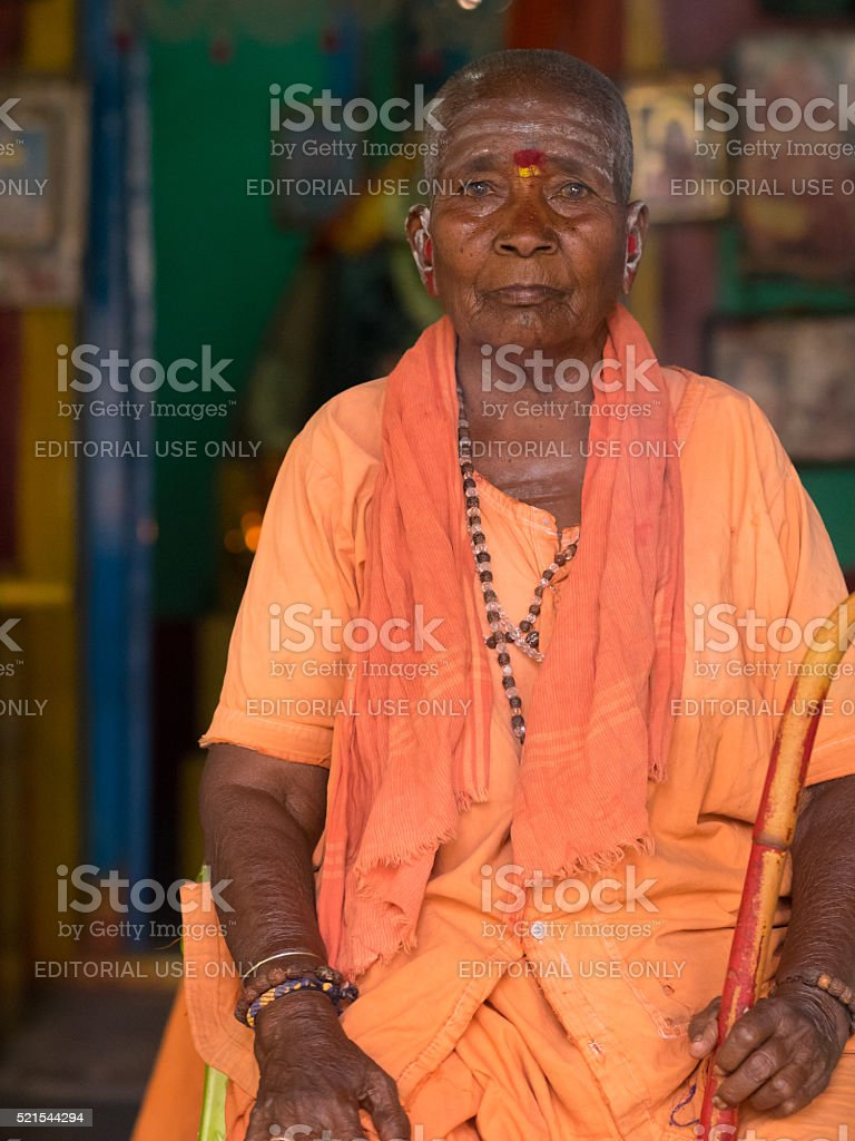 Old India woman sitting in front of Hindu temple stock photo