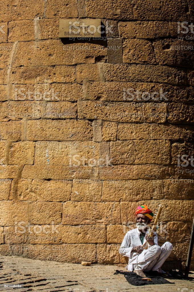 Old indian man sitting inside fort of  Jaisalmer with his musical instrument called ravanhatha stock photo