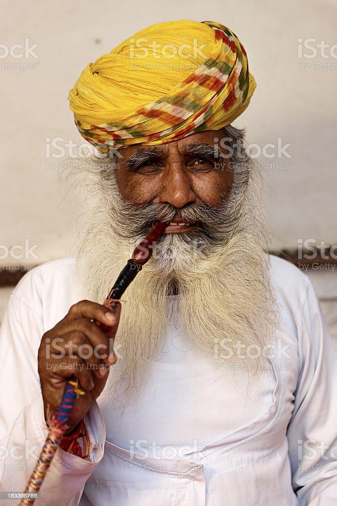 Old Indian man smoking water pipe. royalty-free stock photo