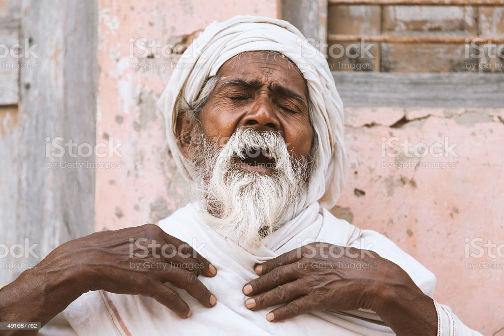 Old indian sadhu speak up sacred scriptures. stock photo