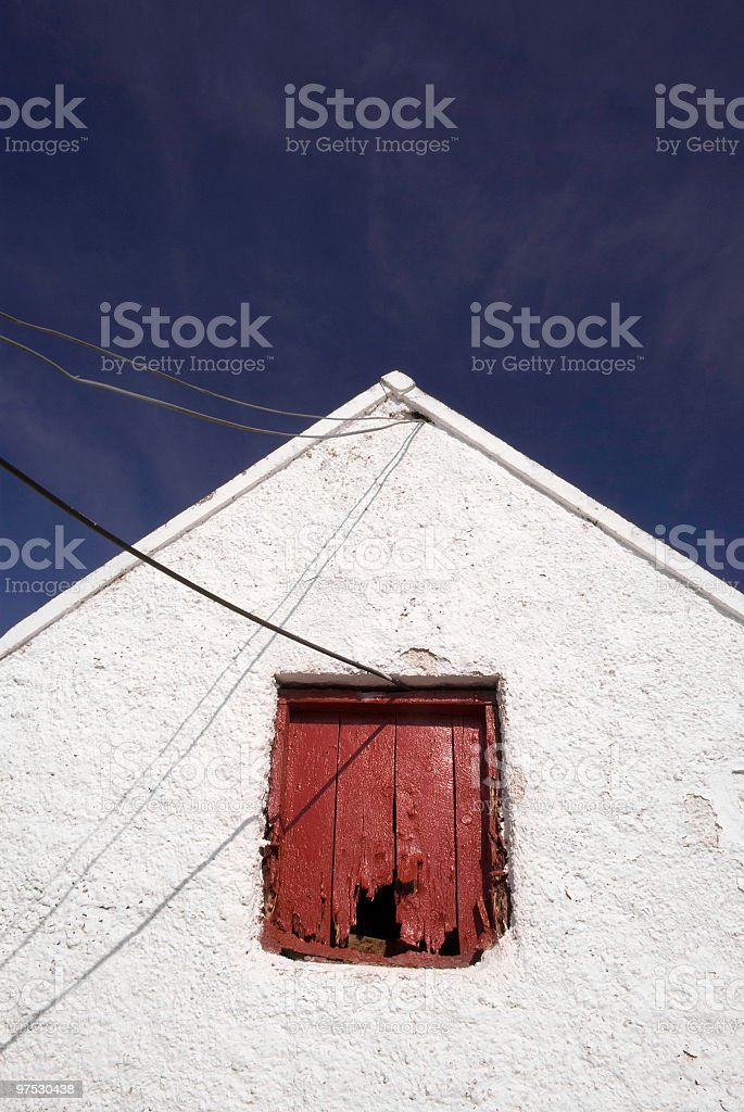 Old Irish farm shed with whitewashed wall and red window stock photo