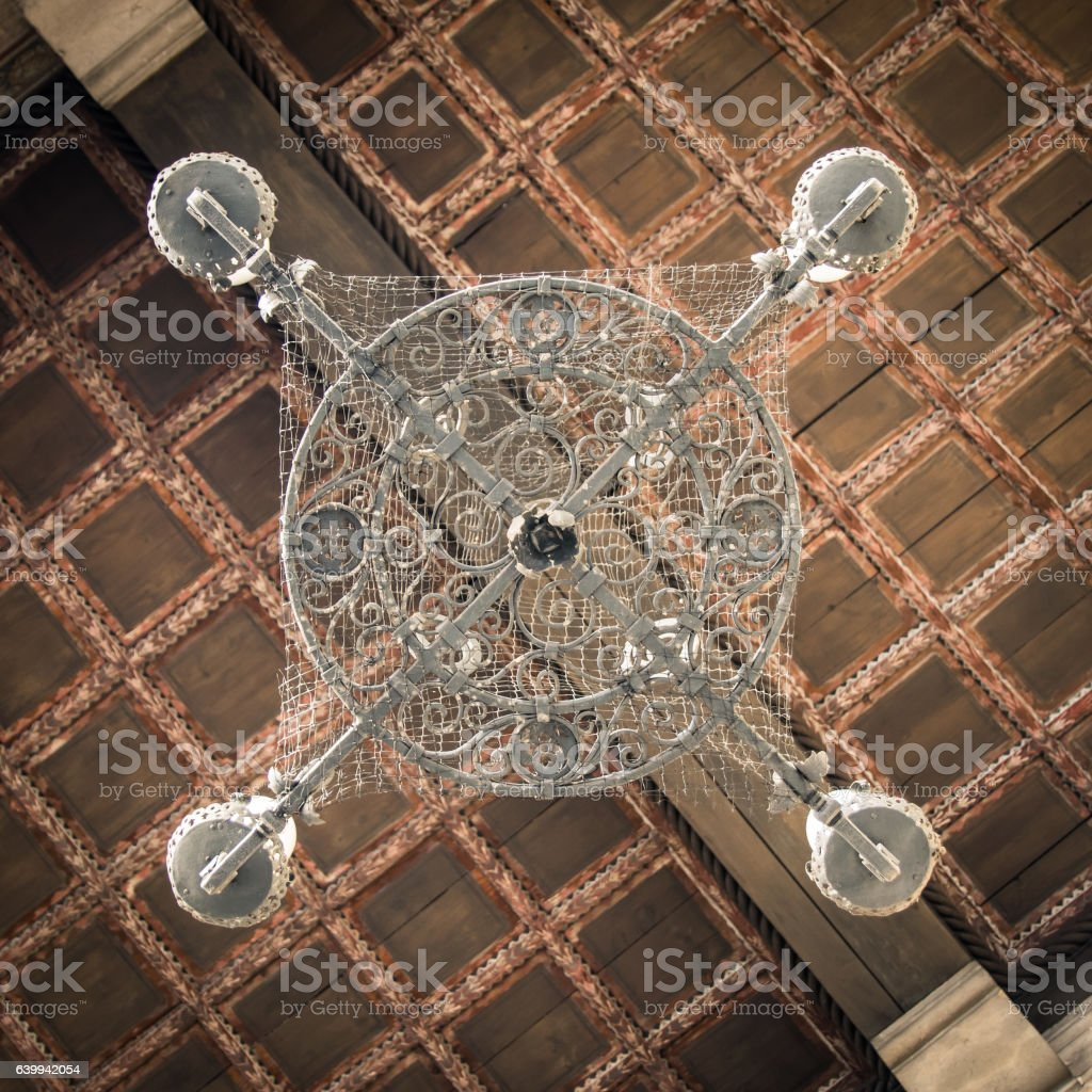 Old iron chandelier and coffered wooden ceiling. stock photo