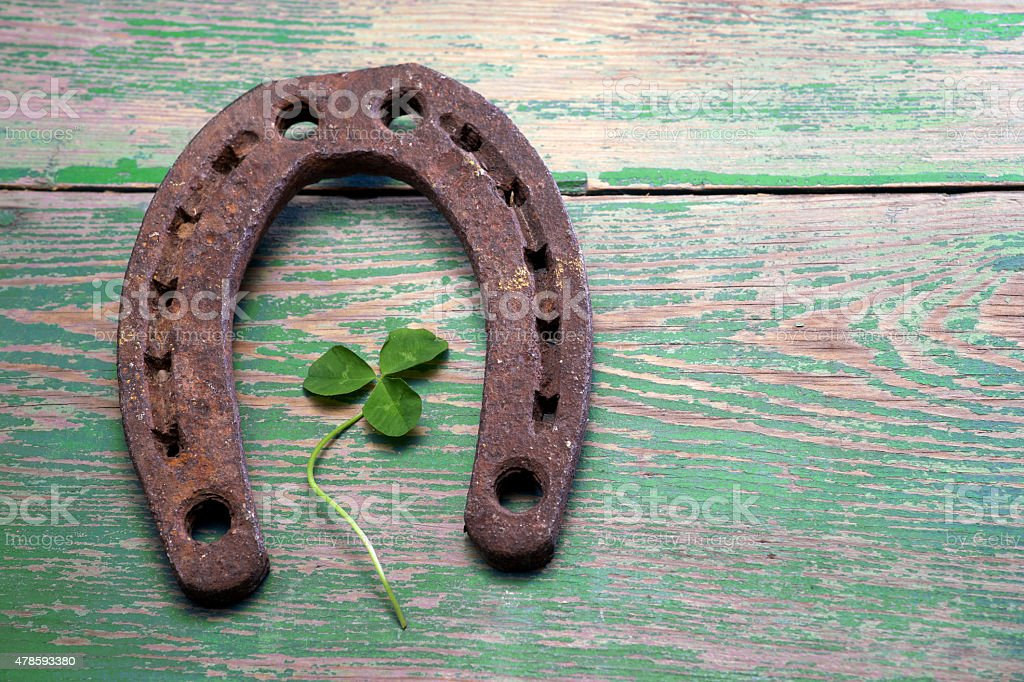 Old iron rusty metal horseshoe on weathered wood stock photo