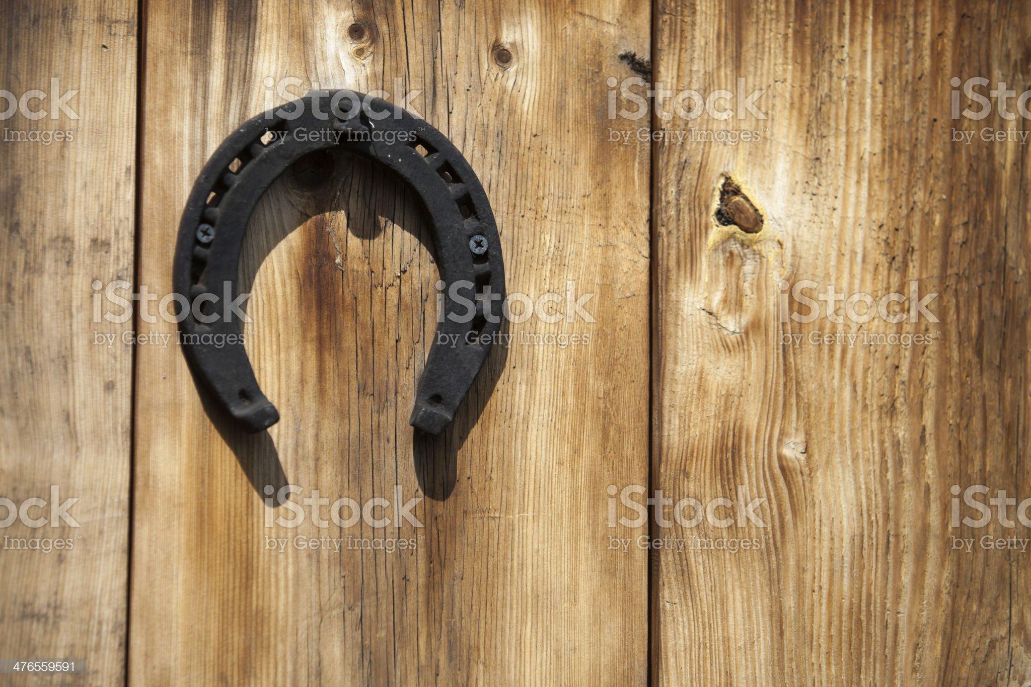 Old iron rusty metal horseshoe on wood background. royalty-free stock photo