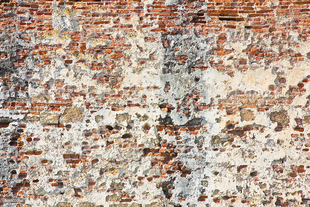 Old italian stone and brick wall with degraded plaster stock photo