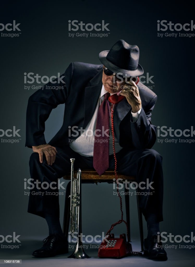 old jazz musician answering a phone call stock photo