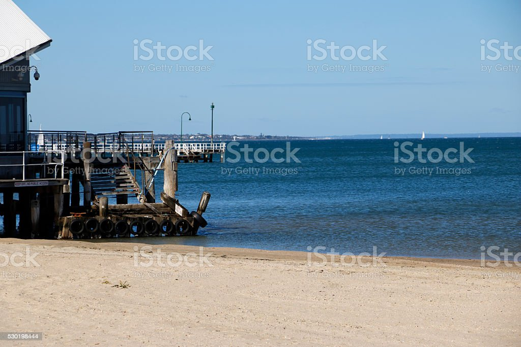 Old Jetty on Beach and Longer Pier in Background stock photo