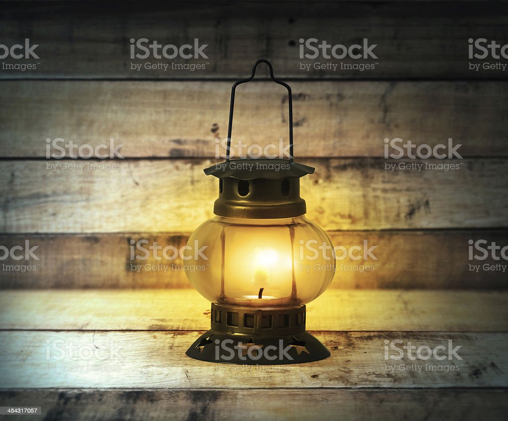 Old kerosene lantern burning with bright flame between wood stock photo