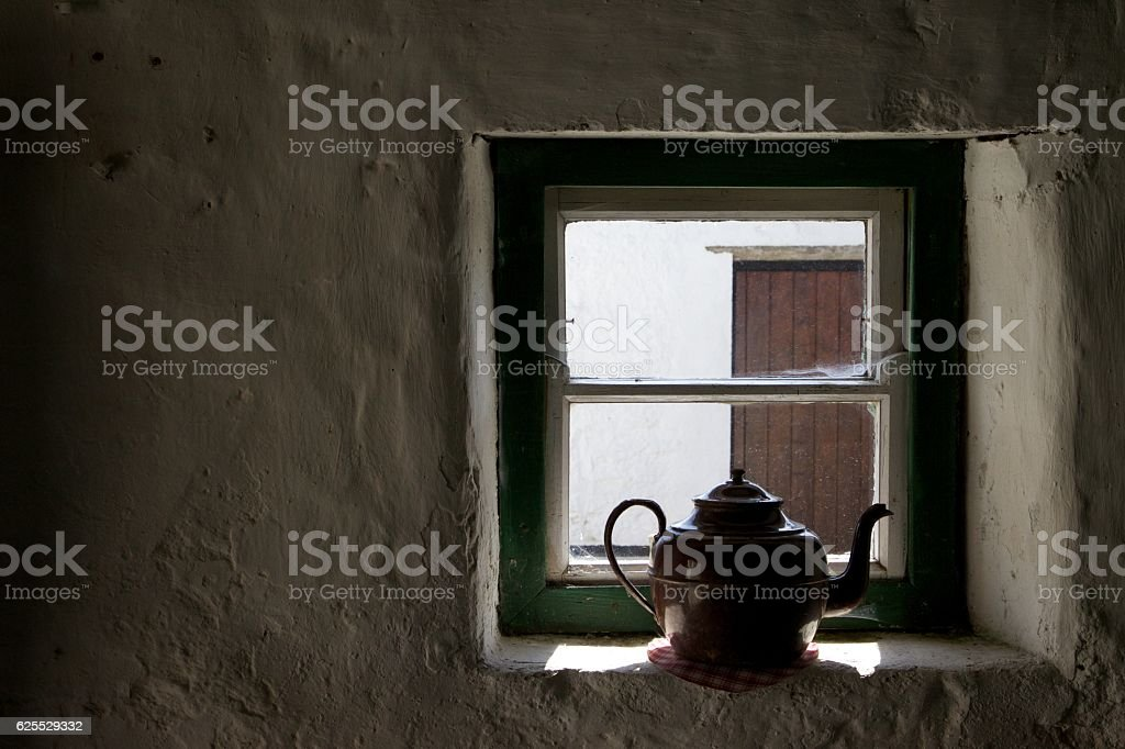 Old kettle in cottage window. stock photo