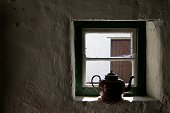 Old kettle in cottage window.
