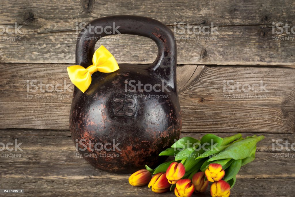 Old kettlebell with a yellow tied bow on a wooden background, gentleman concept stock photo