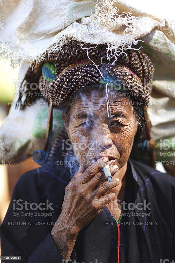 Old Khmer woman smoking cheerot cigarette in Myanmar stock photo