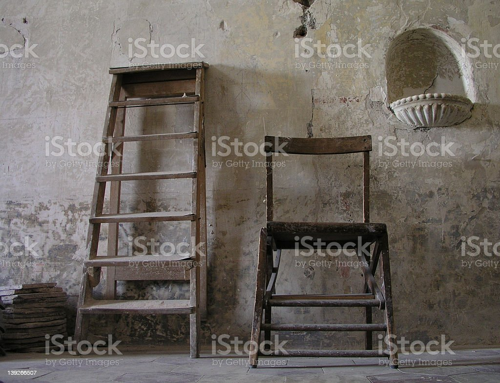 Old Ladder and Chair against wall royalty-free stock photo