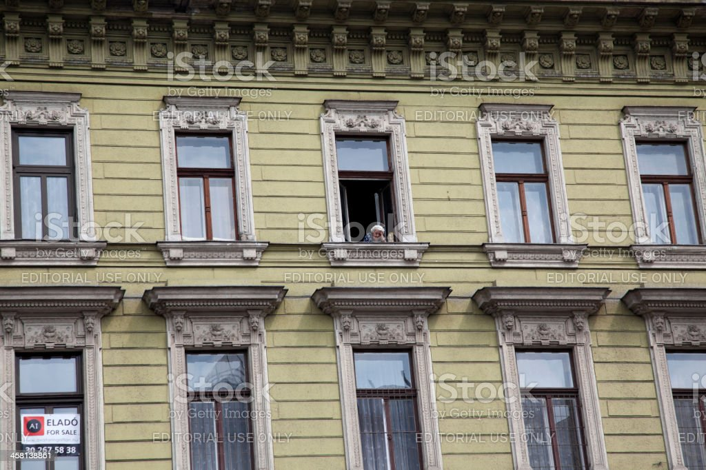 old lady at the window of building in budapest hungary royalty-free stock photo
