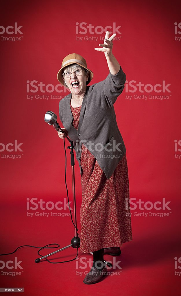 Old lady belts out song into microphone stock photo