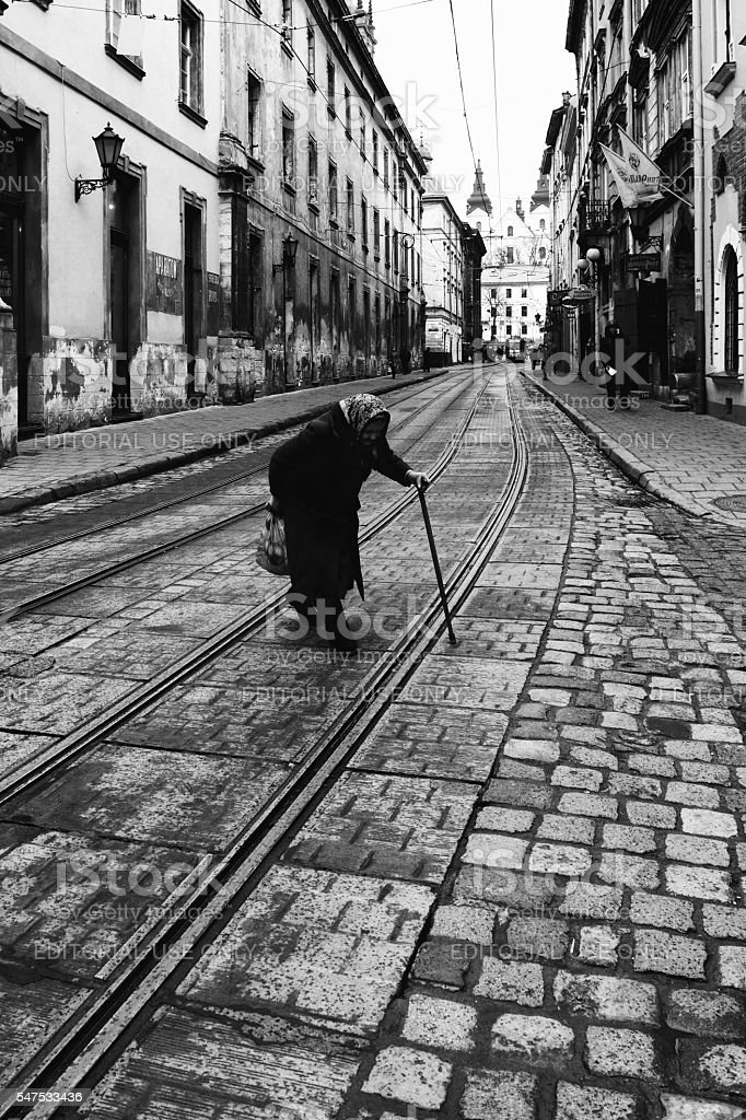 Old Lady crossing street at Lviv stock photo