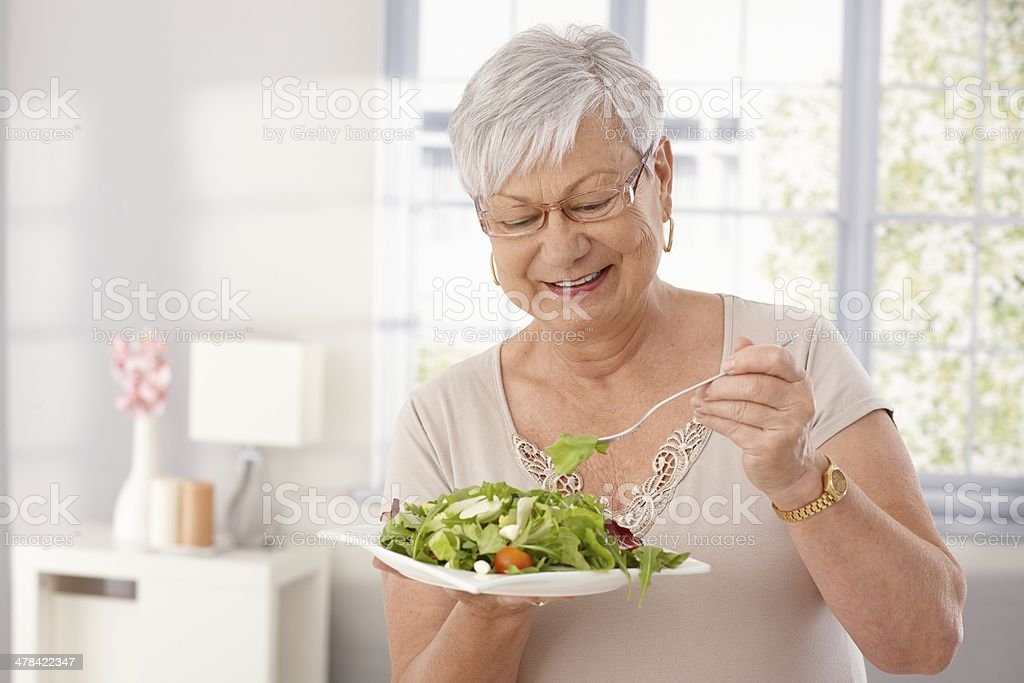 Old lady eating green salad stock photo