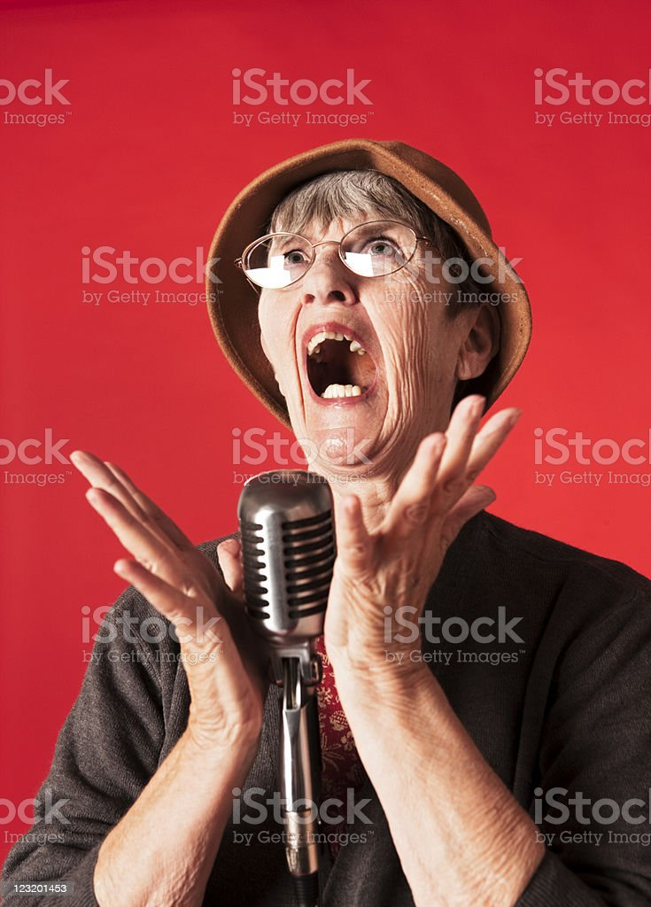 Old lady in front of microphone looks up and sings stock photo