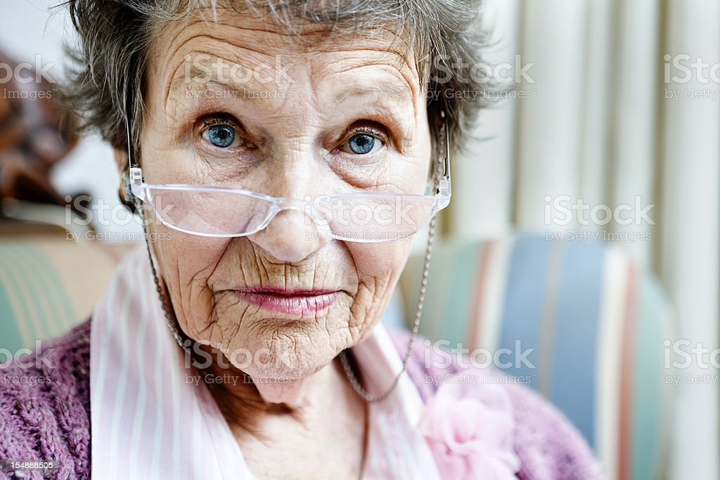 Old lady looks over spectacles, disapproving, eyebrows raised stock photo