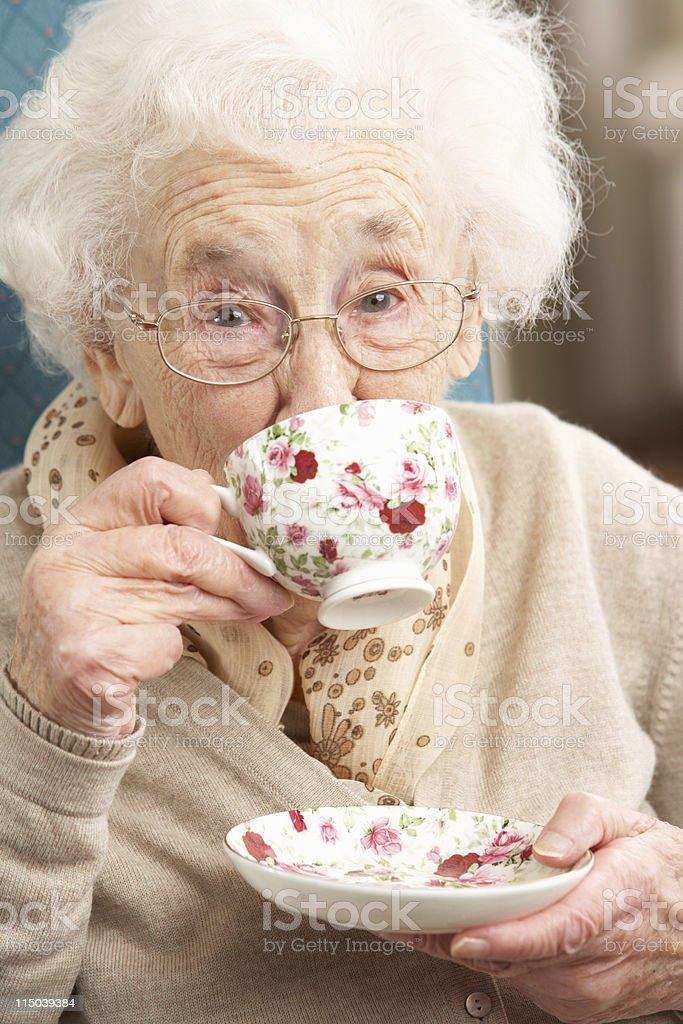 Old lady sipping from a teacup with floral pattern stock photo