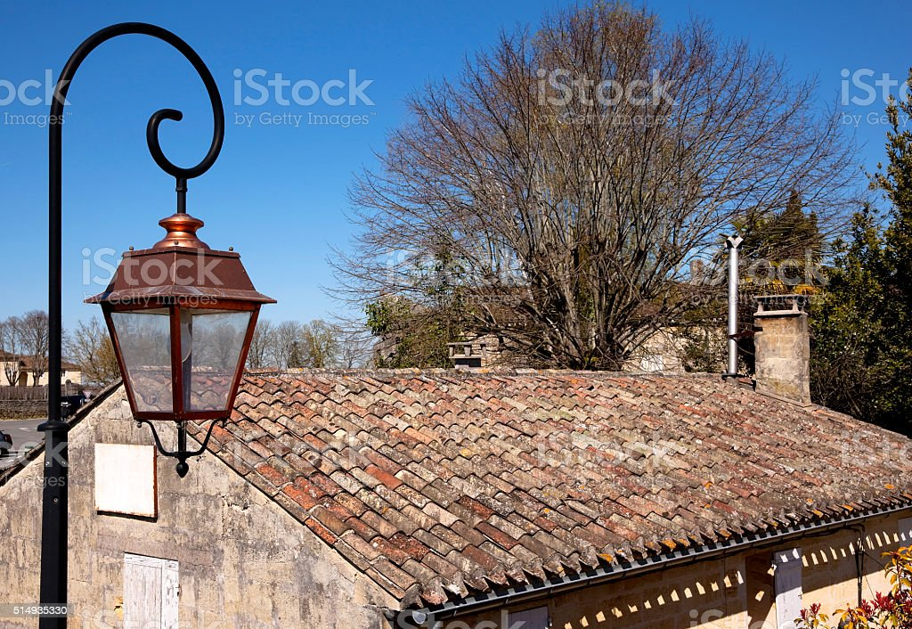 Old lamp post and clay roof in Saint Emilion stock photo