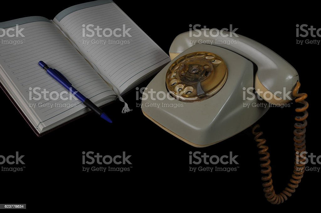 Old Landline Phone by a Notebook stock photo