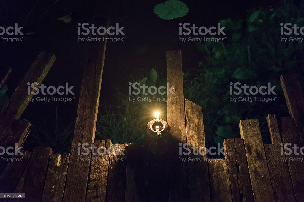Old lantern on wooden floor near pond photo libre de droits