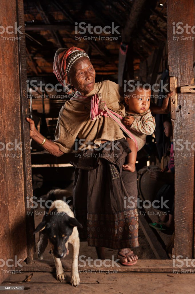 Old Lao woman holding a baby in Northern Laos royalty-free stock photo