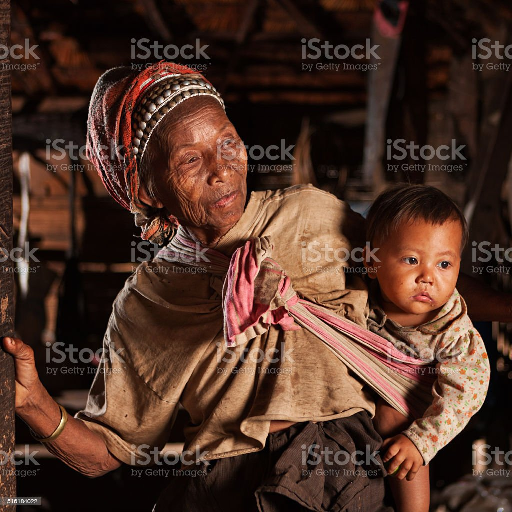 Old Lao woman holding a baby in Northern Laos stock photo
