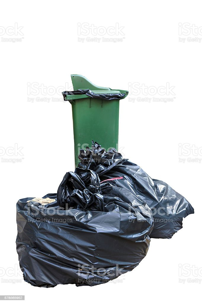 Old large green wheel bin and pile of garbage bags stock photo