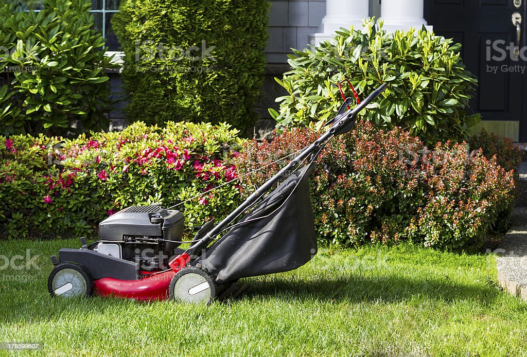 Old Lawnmower on Front Yard Ready for Work stock photo