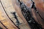 Old leaking rusty oak barrel with wine traces.