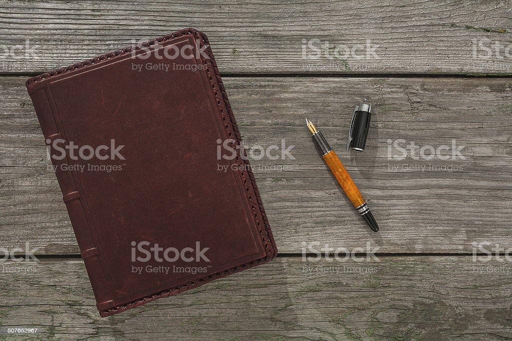 old leather notebook and fountain pen on old wooden boards stock photo