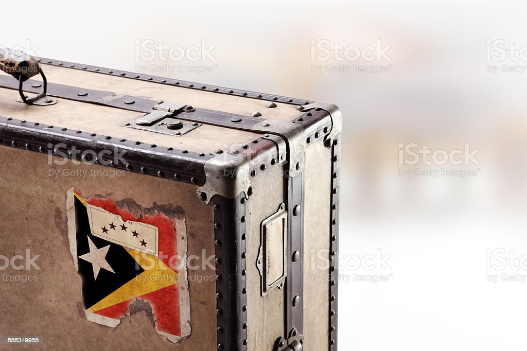 Old leather suitcase with flag of East Timor stock photo
